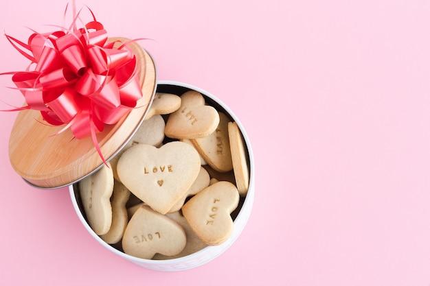 Коробка с печеньем в форме сердца с украшениями на розовом фоне. скопируйте пространство.