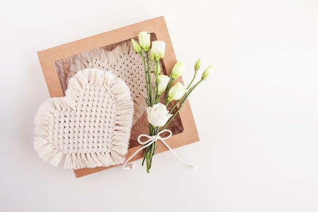 흰색 표면에 마크라메 장식 상자. 천연 소재, 면사. 에코 장식, 장식품, 손으로 만든 장식. 심장-휴가의 상징. 공간 복사