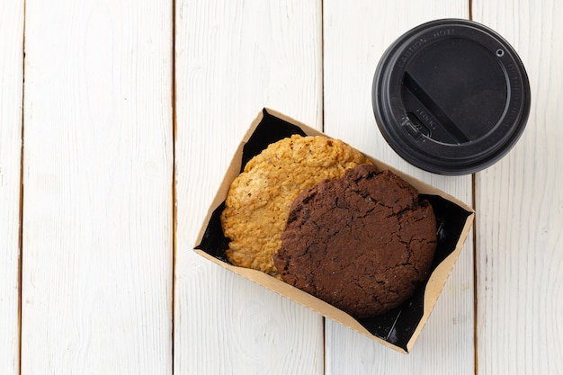 Box with oat cookies and cup of coffee on white wooden table