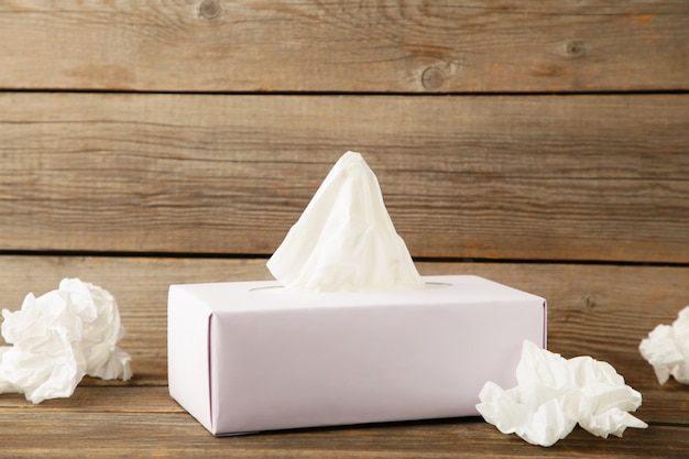 Box with paper tissues and used crumpled napkins on grey wooden
