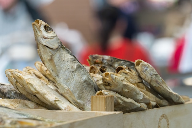 A box with a pile of dried fishes in the beer bar