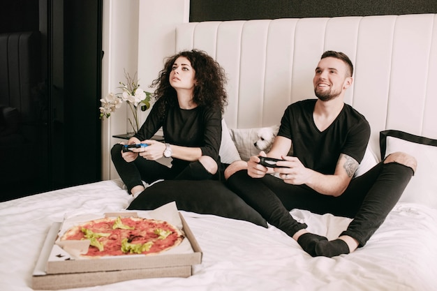Box with pizza stands before man and woman playing on ps on bed