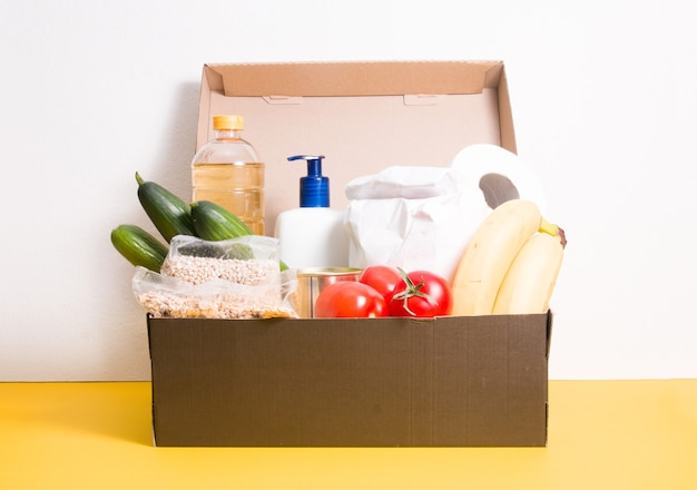 Box with products for donation on yellow surface