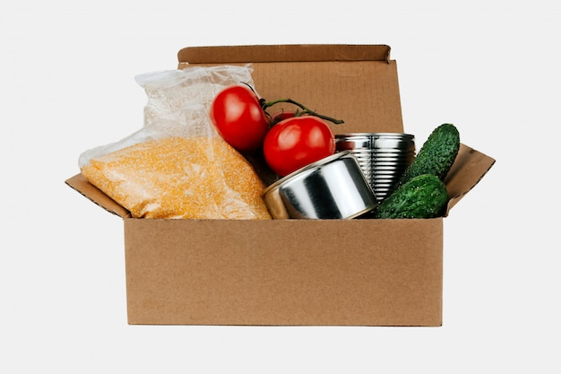 Box with products. vegetables, cereals and canned goods in a cardboard box isolated.