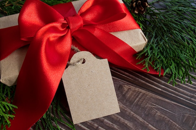 Box with a red bow and a tag for your text on a wooden background.