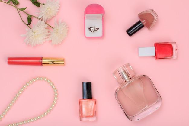 ピンクの背景にリング、ビーズ、香水のボトル、マニキュアと花のボトルが入った箱。女性の化粧品とアクセサリー。上面図。