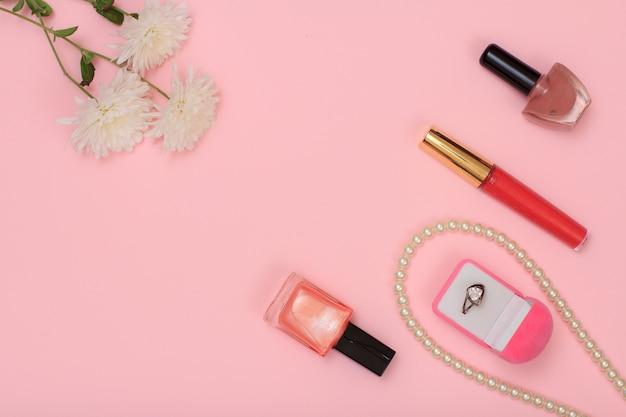 ピンクの背景にリング、ビーズ、マニキュアと花のボトルが入ったボックス。女性の化粧品とアクセサリー。上面図。
