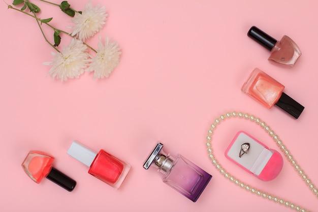 ピンクの背景にリング、ビーズ、マニキュアと香水と花のボトルが入った箱。女性の化粧品とアクセサリー。上面図。