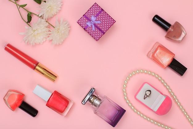 リング、ビーズ、マニキュアと香水のボトル、口紅、ギフトボックス、ピンクの背景に花が付いたボックス。女性の化粧品とアクセサリー。上面図。