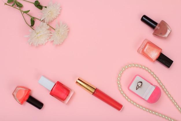 ピンクの背景にリング、ビーズ、マニキュアのボトル、口紅、花のボックス。女性の化粧品とアクセサリー。上面図。