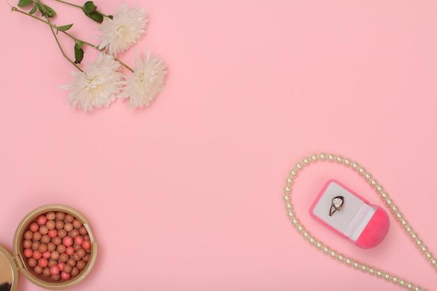 ピンクの背景にリング、ビーズ、パウダー、花のボックス。女性の化粧品とアクセサリー。コピースペースのある上面図。