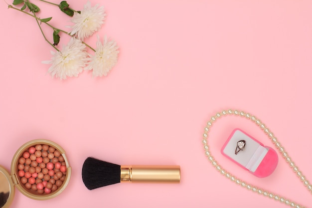 ピンクの背景にリング、ビーズ、パウダー、ブラシ、花のボックス。女性の化粧品とアクセサリー。コピースペースのある上面図。