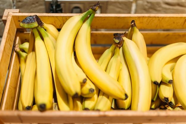 食料品店のスタンドに熟したバナナが入った箱、誰もいない。市場の新鮮な果物