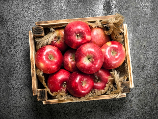 Box with ripe red apples on rustic table.