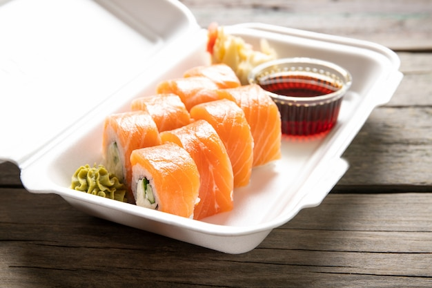 Box with rolls cream cheese soy sauce and wasabi on a wooden background. japanese kitchen. food delivery.