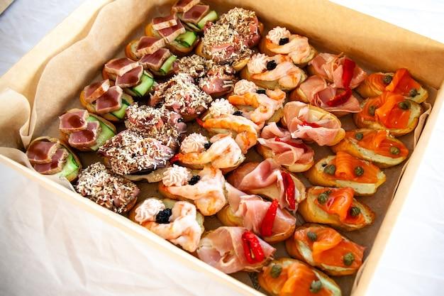Коробка с бутербродами, брускетта с мясным ассорти, сыром и морепродуктами. изысканные закуски для кейтеринга на шведском столе для вечеринки