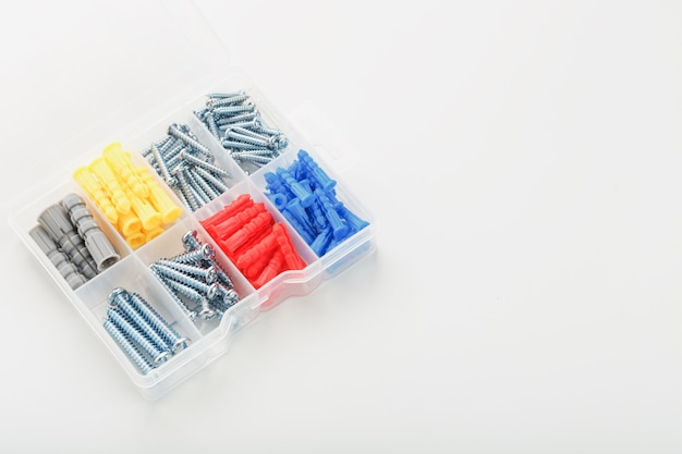 Коробка с саморезами и пластиковыми дюбелями разных размеров, для ремонта и установки. вид сверху