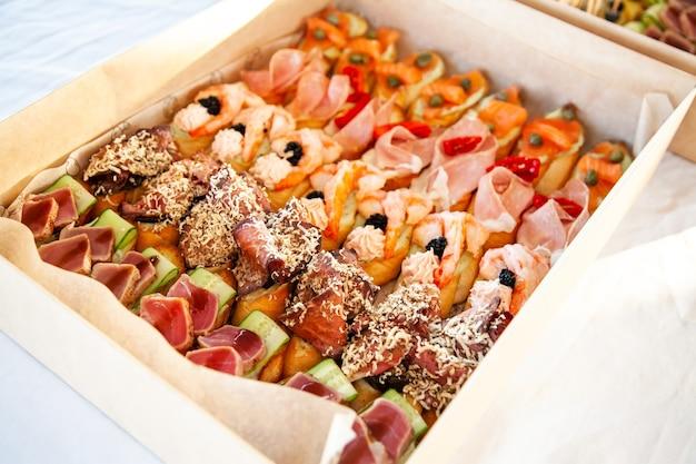Коробка с небольшими бутербродами, брускеттой с мясным ассорти, сыром и морепродуктами для фуршета и вечеринок.