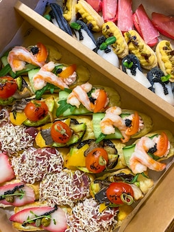 작은 샌드위치, 에끌레어, 냉햄을 곁들인 브루스케타, 구운 야채, 치즈, 해산물이 들어 있는 상자. 샤퀴테리 보드 주문.