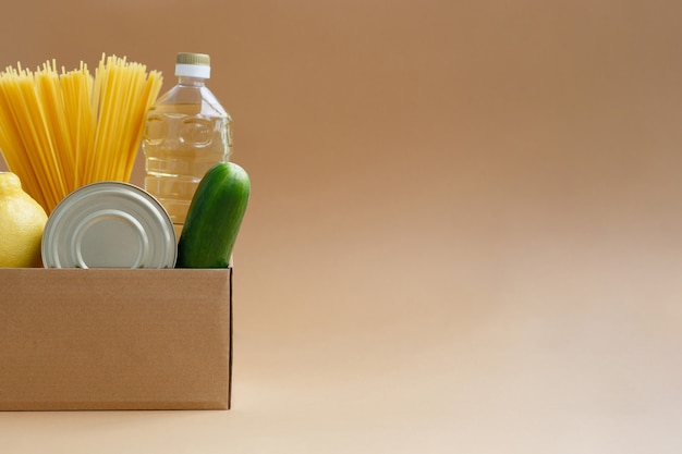 Ящик с запасом еды. дарение товаров нуждающимся. овощи, консервы и макароны