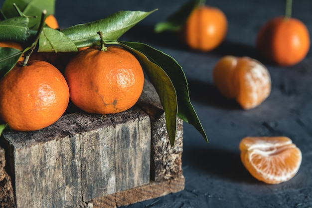 Box with tasty juicy tangerines in wood box on dark