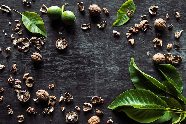Коробка с вкусными грецкими орехами и щелкунчиком на темном деревянном столе, крупным планом