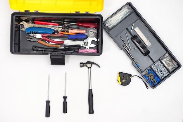 Коробка с инструментами на белой предпосылке. вид сверху составленного молотка с отвертками и рулеткой.