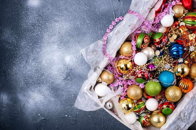 Box with toys of different color for a christmas tree on a black background