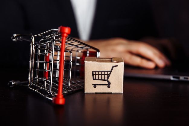 Box with trolly next to laptop. online shopping concept.