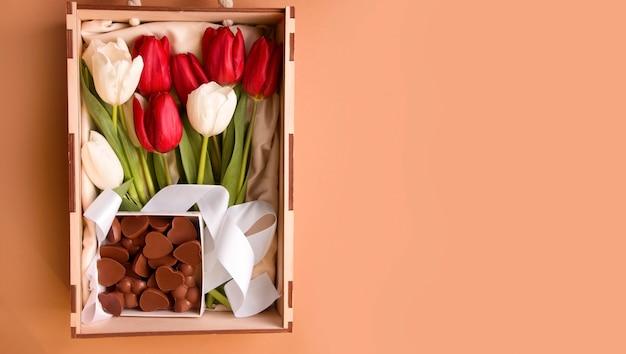 茶色の背景にチューリップの花とチョコレートのボックス。スペースをコピーします。バナー。上から見る