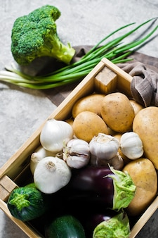 Ящик с овощами: картофель, лук, чеснок, баклажаны, цуккини, брокколи, зеленый лук. ферма.