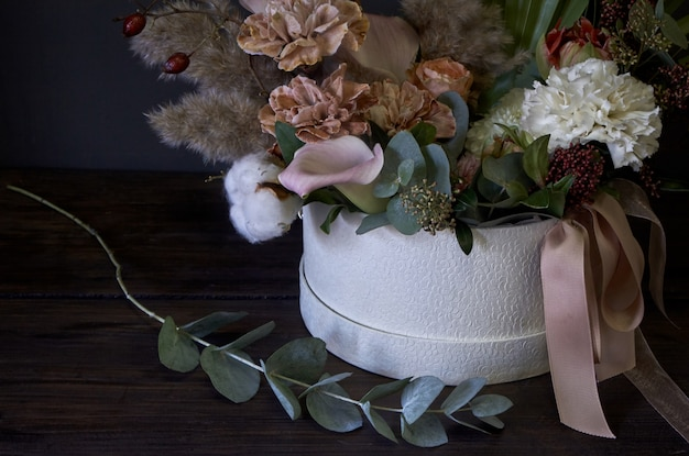 A box with a vintage bouquet and the eucalyptus branch near on a dark background