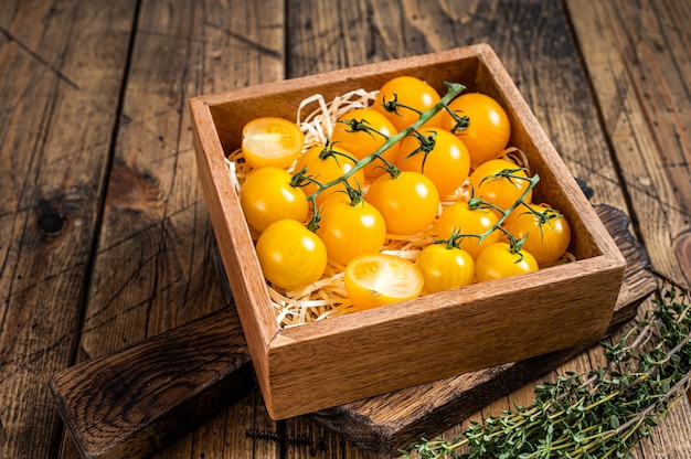 Box with yellow cherry tomato. wooden table . top view.