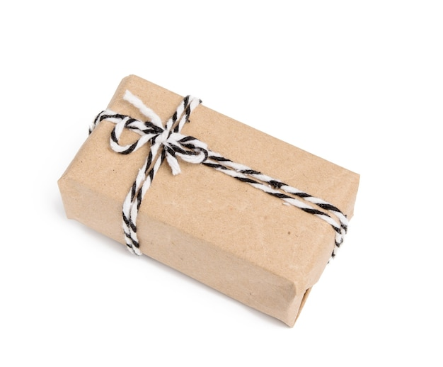 Box wrapped in brown kraft paper and tied with black rope, gift isolated on white background