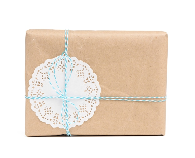 Box wrapped in brown kraft paper and tied with blue rope, gift isolated on white surface
