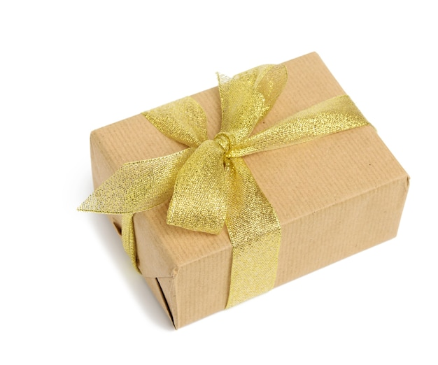 Box wrapped in brown kraft paper and tied with golen ribbon, gift isolated on white background