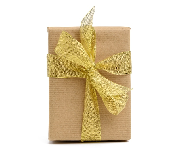 Box wrapped in brown kraft paper and tied with golen ribbon, gift on white background