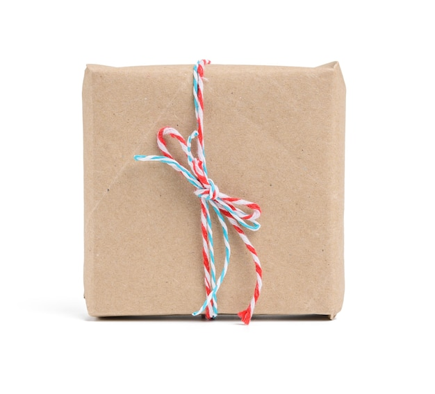Box wrapped in brown kraft paper and tied with red rope, gift isolated on white background