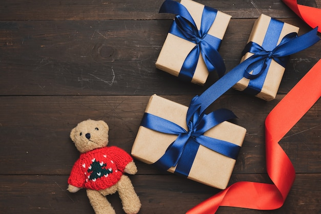 Box wrapped in brown kraft paper and tied with red silk ribbon on brown wooden background, top view