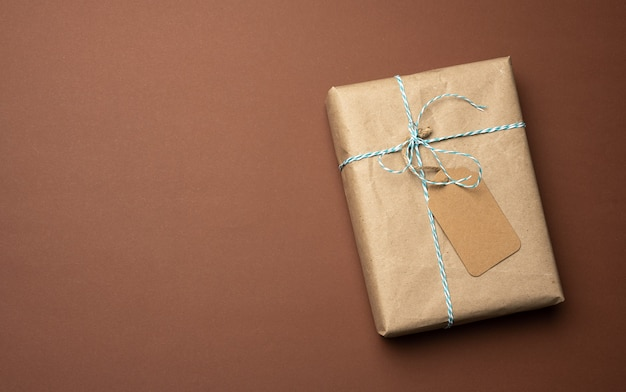 Box wrapped in brown kraft paper and tied with rope, gift on a brown background, top view