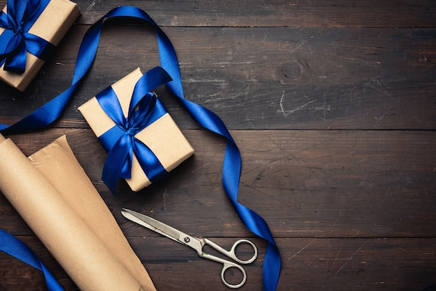 Box wrapped in brown paper and tied with a blue silk ribbon with a bow, gift on a brown wooden background, top view, copy space
