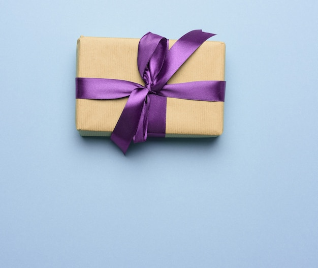 Box wrapped in brown paper and tied with a purple silk ribbon with a bow, gift on a blue background, top view