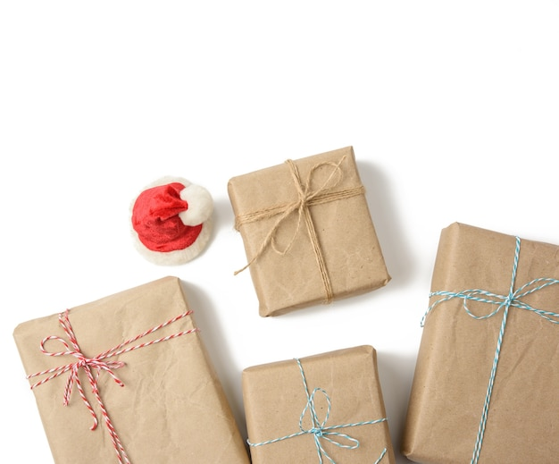 Box wrapped in brown paper and tied with rope, gift on white, top view