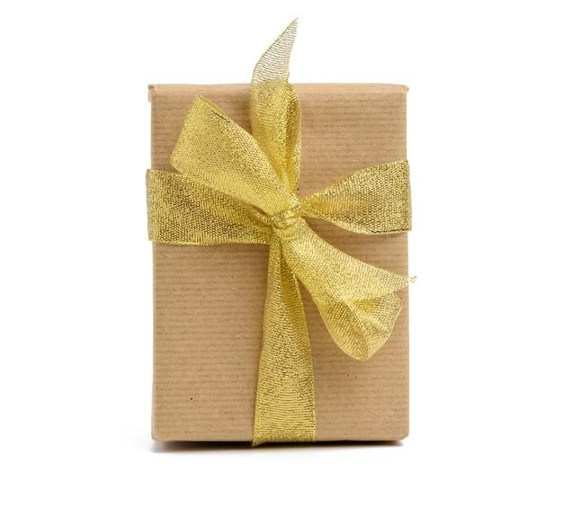 Коробка, завернутая в коричневую крафт-бумагу и перевязанная голеновой лентой, подарок на белом фоне