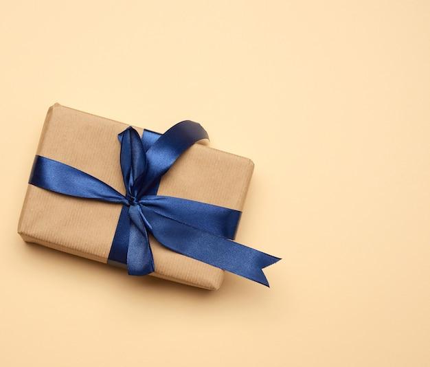 Коробка, завернутая в коричневую бумагу и перевязанная синей шелковой лентой с бантом, подарок на бежевом, вид сверху