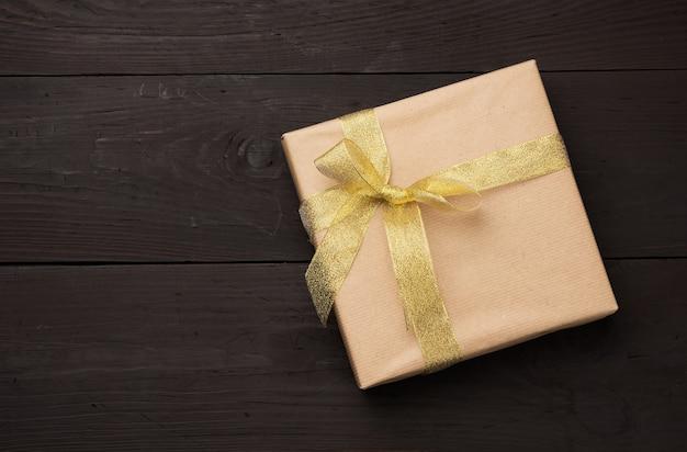갈색 종이에 싸서 활과 황금 리본으로 묶인 상자, 나무 배경에 선물, 평면도