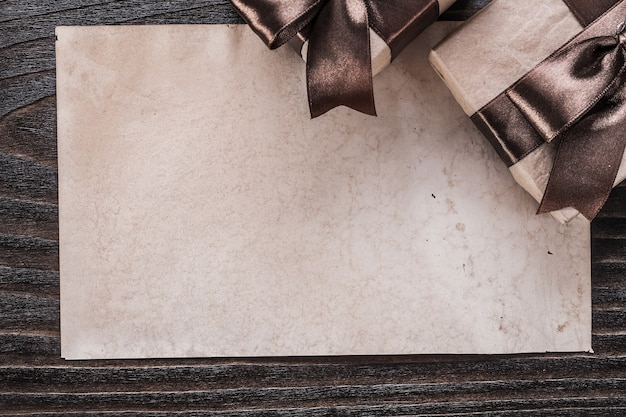 Boxed gifts with tied brown bows paper on wooden board.