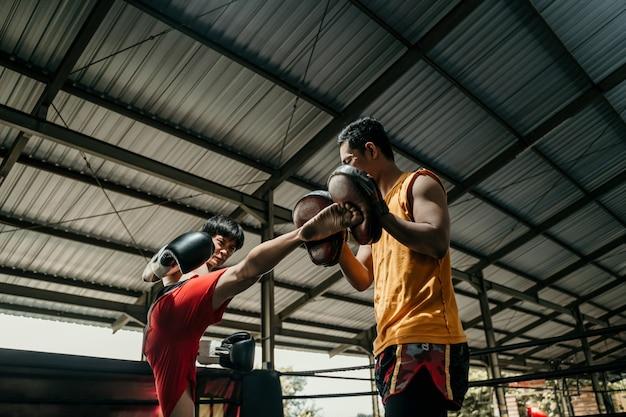 권투 선수와 그의 코치는 링에서 스파링을하고 있습니다. 권투 선수와 그의 코치는 몇 가지 동작을 연습