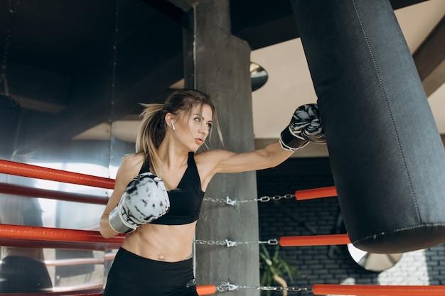 Boxer athlete training boxing punching bag enjoying intense exercise muslim