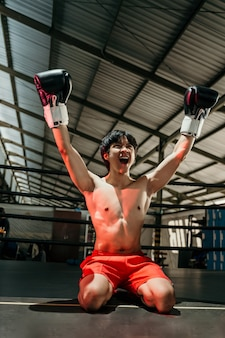 Boxer in boxing gloves when winning raises both hands sitting on the floor of the boxing ring